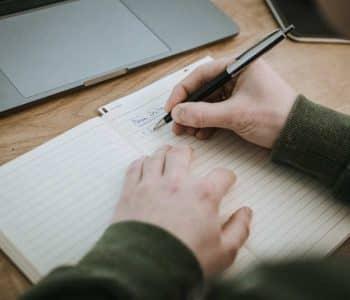 Mann schreibt in ein Notizheft seine guten Vorsätze zum Intervallfasten